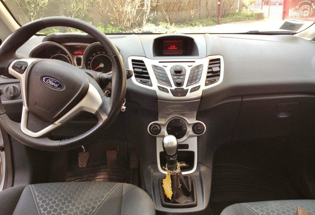 in questa foto si vede l'abitacolo della Ford Fiesta 6 con il volante, l'autoradio, i sedili e la plancia/cruscotto