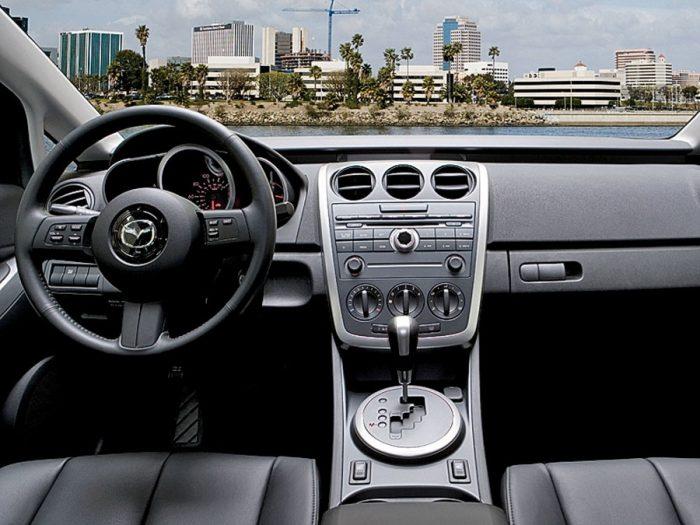 in questa foto si vede l'abitacolo della Mazda CX-7 con il volante, l'autoradio, i sedili e la plancia/cruscotto