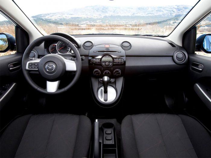in questa foto si vede l'abitacolo della Mazda 2 DE II con il volante, l'autoradio, i sedili e la plancia/cruscotto