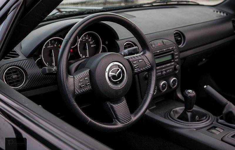 in questa foto si vede l'abitacolo della Mazda MX-5 NC III con il volante, l'autoradio, i sedili e la plancia/cruscotto
