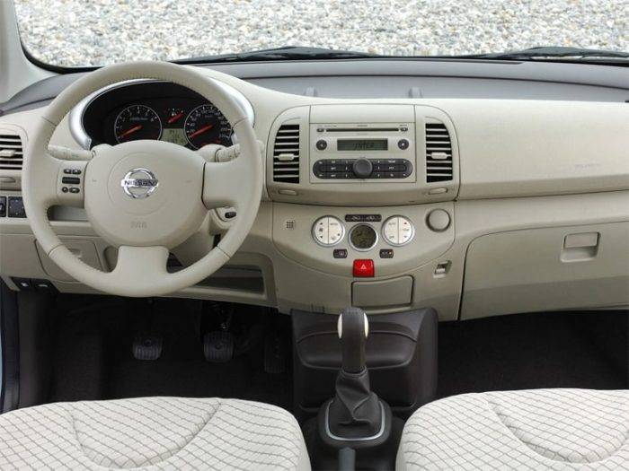 in questa foto si vede l'abitacolo della Nissan Micra III con il volante, l'autoradio, i sedili e la plancia/cruscotto