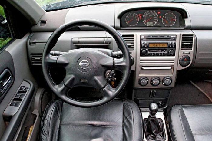in questa foto si vede l'abitacolo della Nissan X-Trail con il volante, l'autoradio, i sedili e la plancia/cruscotto